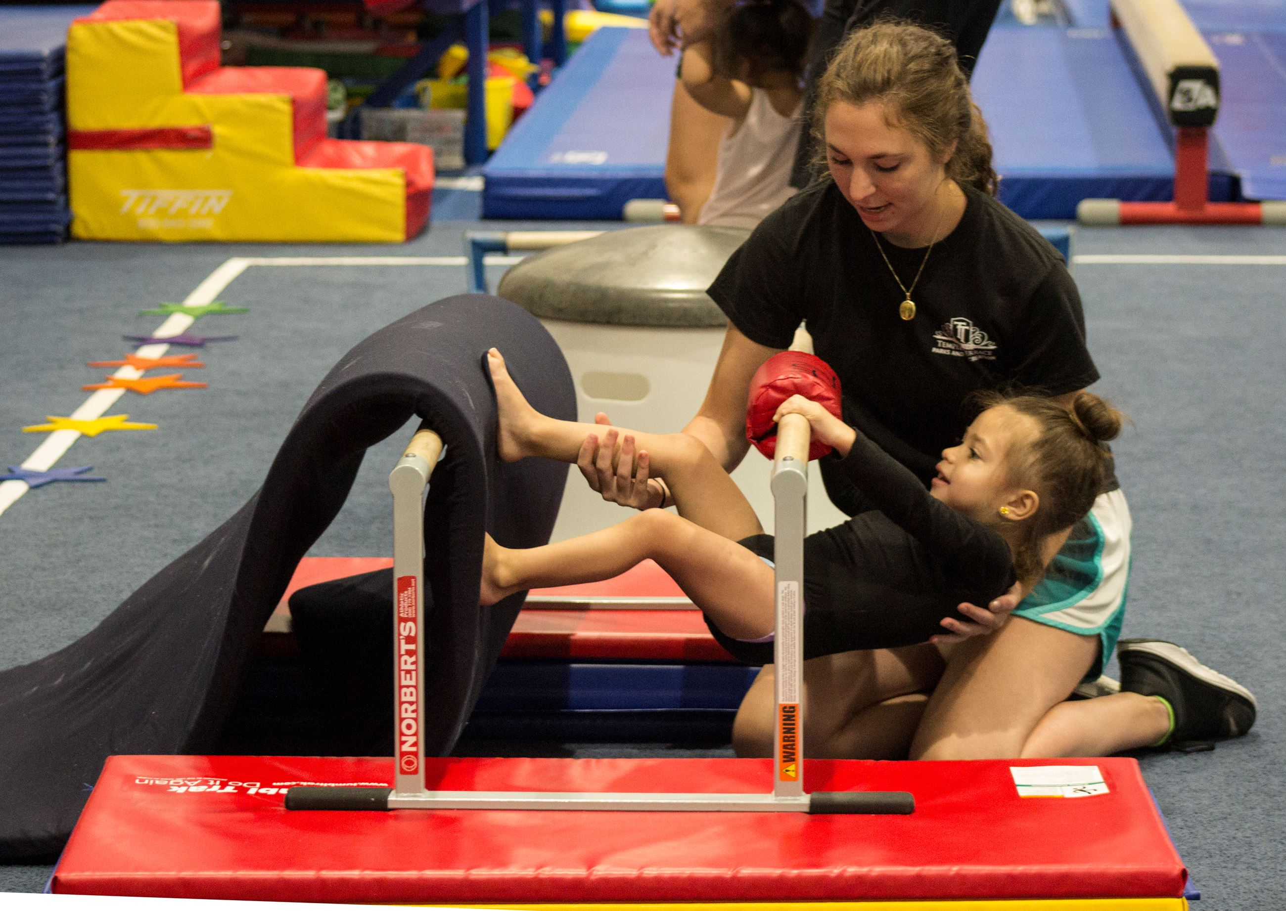 A gymnastics instructor helps a child tumble